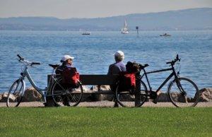 Personas mayores sentadas en un banco con bicicletas